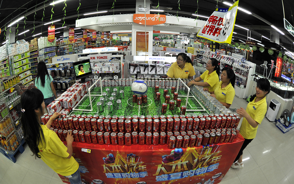 一些超市抓住世界杯商机,啤酒饮料柜台布置成球场造型,摆放电视机播放